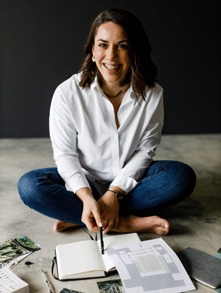 Photographic portrait of the event & wedding planner and founder of Brava, Soraia Santos, smiling and sitting on the floor surrounded by her notebooks, inspirations, plans and notes.