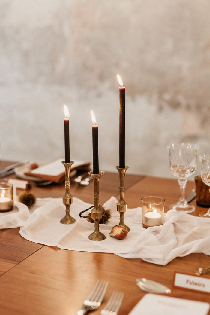 Detail of the styling and decoration of the meal table at the small Brava's launch event, where three brass candlesticks with lighted candles stand out, in an intimate and cozy atmosphere.
