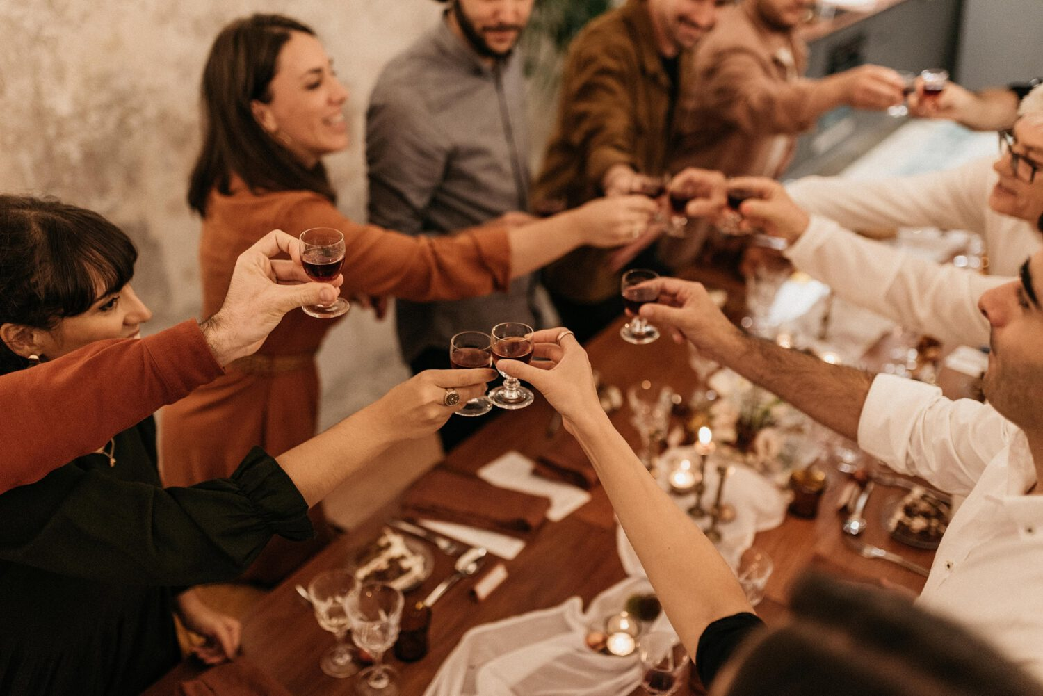 Standing guests toast between smiles around the meal table at the Brava launch event, in a cheerful and cozy atmosphere, like a small and intimate wedding.